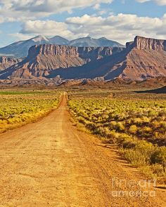 A dirt road leads toward buttes and the La Sal mountains outside Moab, Utah. A very inviting view.
