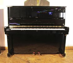A 1995, Steinway Model K upright piano with a black case and brass fittings at Besbrode Pianos £20,000. Piano has an eighty-eight note keyboard and two pedals.