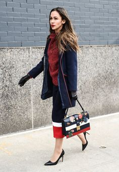 Bundled up in a navy coat, wine sweater, with a contrasting colorblocked midi skirt and printed satchel