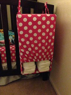 DIY- Diaper holder out of crib sheet and diaper box. I couldn't find a diaper stacker to match my daughters new crib bedding. So had the idea to use the same crib sheet which I found at target to make my own. I used an old diaper box, cut a small opening at the bottom and glue the crib sheet to fit the box. I used the Elastic to tie it to the crib. I had 4 small hopes, two on the top corners and two on the back side.  I loved how it came out. Super excited to finish her crib