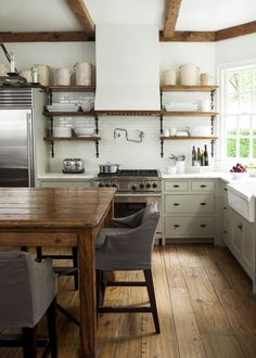 white kitchen with exposed beams, open shelves, farm table, crocks, white dishes, and pot filler faucet