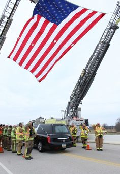 Frederica and Bowers volunteer firefighters salute the hearse carrying Lt. Steven Floyd. Delaware State News photo by Andrew West