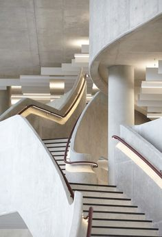 Snaking around the perimeter of this office, a grand concrete ascends between all four floors and also integrates balconies.
