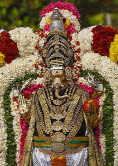 beautiful-india:  Golden Statue Of Lord Ganesha Adorned With Flowers And Holding An Apple During Masi Magam Festival, Pondicherry, India by Eric Lafforgue on Flickr.