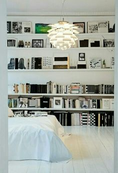 Bedroom - white painted floor, wide shelving, low bed.