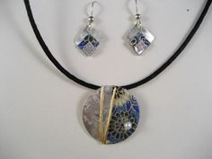 Sterling Silver disc embellished with Japanese Washi paper in antique blue. A light glaze protects. Approximately 1 inch diameter disc that slides on an adjustable black silk cord - longest length 24 inches, shortest is 18 inches. (seen with 3 tier drop earrings)