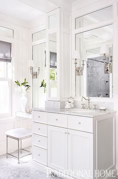 Monochromatic bathroom with white vanity accented with crystal pulls and white marble counters ...