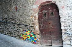 Street artists worldwide are beautifying crumbling streets, walls, and buildings by filling in the holes with LEGO bricks — which not only makes old structures whole again, but gives the illusion that they're LEGO buildings that have been camouflaged with plaster or stone.