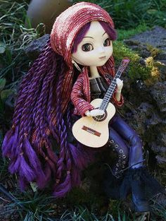 Pullip Nomado February 2004 doll. The place I am in is my stage. My song will reach to you, to anywhere!!... Feel like so. Pullip type 2 body. Rooted long hair in purple dreadlock braids, with violet eyes in bohemian makeup. She wears a large gold hoop earrings, with tube top, hippie lace-up pants, boots, a jacket with a matching head scarf and a Guitar. Nomado does not come with a doll stand.