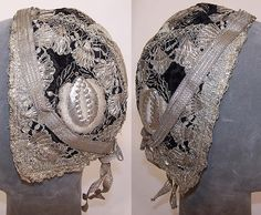 This antique silver metallic embroidered black velvet German folk bonnet cap dates from the early 19th century. It is hand stitched, made of a black silk velvet fabric, with silver bullion metal thread lace trim, raised padded satin stitch embroidery couching stumpwork and hand sewn metallic sequins. There is a silver metallic ribbon bow trim on the bottom back.
