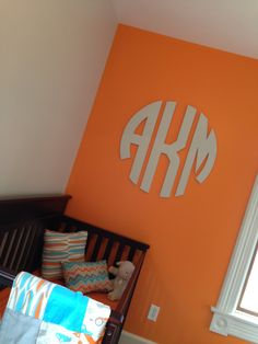 This preppy wall monogram from @spottedzebras really pops on the orange accent wall in the nursery!