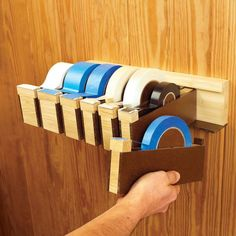 Tapes-To-Go Wall-Hung Dispensers Woodworking Plan from WOOD Magazine - Hang them at a convenient height, and lift off only the dispensers you need. Start by determining how many rolls of tape you use in your shop. Then, create a dispenser for each from this plan.