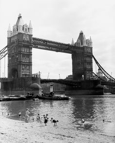 Children enjoy the summer in the centre of London, paddling in the River Thames on a man made beach with Tower Bridge in the background.Dat...