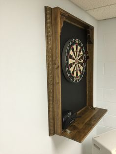 DIM (did it myself) dartboard cabinet--  homasote backboard catches stray darts, fold out shelf conceals cabinet contents, and provides a place to put your drink