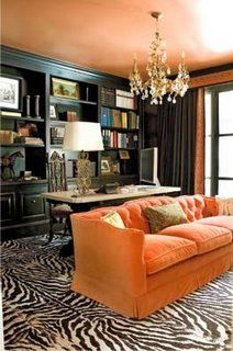 large zebra area carpet, complete with straight edges, orange sofa & ceiling, wall of shiny black bookcases.