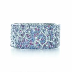 Night-blooming flowers gather in dramatic prelude to evening. Bracelet of Montana sapphires ranging from blue to violet, and diamonds forming a tender branch of leaves, in platinum.
