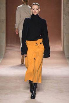 Victoria Beckham zeigt eine Herbst/Winter-Kollektion 2015/16 in New York aus tollen Kleidern und Outerwear mit einer Liebe zum Detail, insbesondere Asymmetrie und Drapierungen. So finden sich an der Hüfte gebundene Stoffe neben großen Knöpfen und schräg verlaufenden Säumen.