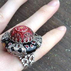 Ollipop USA Artsy Filigree Blown Glass Cocktail Excellent condition. Made in USA. Silver tone swirls, architecture cut out band and bold clasp. Celtic. Paisley. Swirly. Gypsy queen. Bohemian muted red. Maroon painted circle dome. Floral shrinky dink black stone encased. Gorgeous art piece. Fancy party. Collectible. Evening or business professional. Statement ring. Art Deco. Vintage flare. Ollipop Jewelry Rings