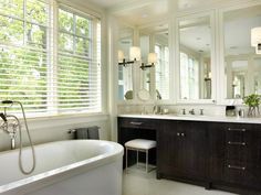 """In a master bath designed for a couple, JamesThomas Design created a space with rich architectural detailing and a simple black-and-white color scheme. Above the his-and-hers vanity, the design team fixed mirrors in frames with a mirrored medicine cabinet between the two mirrors. """"The three mirrored panels reflect the windows above the tub, bouncing an abundance of morning light throughout the space,"""" say the designers."""