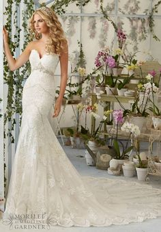 Styled in tulle adorned with embroidered appliques, this Mori Lee 2825 fit and flare wedding dress has a scalloped edged, plunging sweetheart neckline. Crystal moonstone beading creates an inverted empire waistline on the strapless bodice, mirroring the scalloped edged insets that adorn the gown. Covered buttons accent the semi-open back. The skirt and inset cathedral train finish in a scalloped edged, lace border hemline.