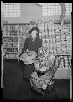 Kroger Store; 726 East Main; interior; woman standing beside her shopping basket holding a basket of grocery coupons, 1948. Part of Lafayette Studios photographs: 1940s decade, 1940-1949.