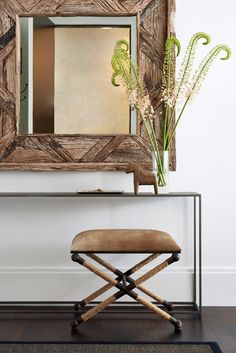 In the entryway, a rustic mirror by Studio|A—built using bits of salvaged wood—is complemented by a slim metal console from CB2 with a raw antiqued finish. The cowhide stool with rope-wrapped iron legs is from Mecox.