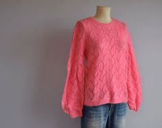 Super soft and light weight wool and mohair blend is knit in a jewel neck style in a beautiful shade of heather raspberry pink. Pretty open and lacy