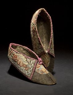 """Huron Embroidered Hide Moccasins from the John Painter Collection of American Indian Art. Wow, look at the gorgeous embroidery! 1800, thread-sewn black-tanned hide with extraordinarily fine floral moosehair embroidery on vamps and cuffs using colors of blue, red, pink, yellow, and white; cuffs edged in purple satin ribbon, length 9"""". Huron (Quebec), Shoes, moosehair/silk/leather, c. 1800."""