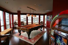 The ideal man cave need not be dark as long as it is multi-functional. A jukebox and billiard table are just the beginning. The comfortable seating and deep burgundy walls, along with nice lighting and an Oriental rug, illustrate that a man cave can be an attractive room in the house rather than a sloppy and grungy corner.