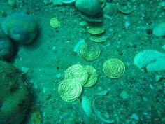 <p>RUNDT 2000: Dykkere viser fram noen av de mer enn 1000 år gamle gullmyntene som ble funnet på havbunnen i havnen i den israelske oldtidsbyen Caesarea.</p>
