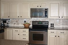 LOVE the cream color painted kitchen cabinets with dark hardware. I like a stone backsplash but not really this one.