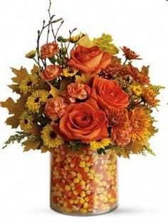 Autumn centerpiece - use 2 clear vases, one smaller than the other, fill the outer void with candy and the inner vase with fall flowers!