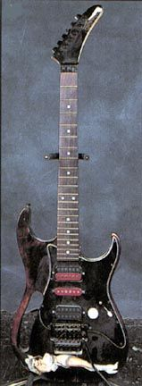 "Steve Vai's Performance Jem Custom No Serial Number One of the first prototype Jem guitars, built by Performance Guitar in Hollywood, California, before Ibanez started working on the Jem guitars. This guitar features 1940's World War II bomber style artwork on a see-through dark tobacco finish. Notice the early monkey grip, much different than the grips used on typical Ibanez Jems. This guitar was used extensively on the 1986 David Lee Roth ""Eat 'Em & Smile"" world tour."