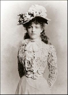 Portrait of a beautiful young lady wearing an equally beautiful hat and lace bodice. Looks like she is wearing her hair down.