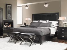 A grayscale palette ranging from snowy white to deep onyx works perfectly in this glamorous master bedroom. Reflective surfaces, such as nailhead trim on the stools and headboard and mirrored ball pendants above the bed, add luster to the luxurious mix.