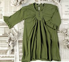 A few easy steps turn a frumpy tee into a standout tunic.  -sans the ruffles and substitute something edgier for the buttons,. Wish I could sew...  Any volunteers to help?