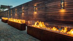 "Komodo Outdoor Linear Fire Pit | CSA CE Certified | Paloform North America UK Europe Custom models shown in Corten steel with lava rock topping and glass shield.Available in 84"" or 60"" lengths. 6 fire pits in 12' lengths line a feature wall at Galleria Marchetti in Chicago."