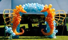 Balloon sculpture of two sea horses with the blue balloon arch on the background.  Some lucky lady was two years old that day!      wowballoons.com