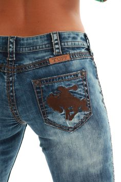 Oh My Gosh, buckin' horses! Remake of the 2013 spring top seller, OMG jean with some serious cowgirl attitude. Brown buckin' horse embroidery on back pockets and matching thick triple line brown stitching throughout all seams. Heavy bleaching give this jean its unmistakable style. Medium wash denim. Cotton/spandex.  #JWIWOG #cowgirltuff