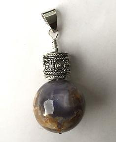 Pendentif Calcédoine bleue et Argent. La pierre est une sphère de Calcédoine bleue et sa roche mère de couleur marron-beige, surmontée d'un très jolie perle d'Argent travaillée.