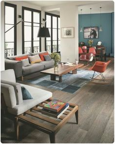 White&blue living room with touch of orange (orange cushions, orange Eames  rocking chair,...)