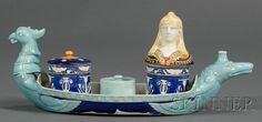 Wedgwood Majolica Egyptian Ink Stand, England, c. 1875, polychrome decorated, the tray modeled as a ship with a griffin's head at the prow and a crocodile's at the stern, set with a covered canopic jar inkpot, sander, and covered jar, each adorned with Egyptian motifs.