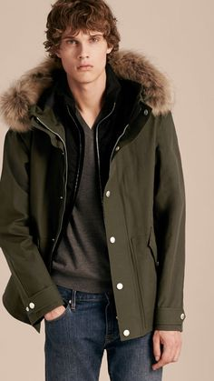 A resilient bonded cotton Burberry parka jacket for colder climates with snap closure pockets and detachable raccoon fur at the drawcord hood. The adaptable design has a down-filled quilted gilet to seal in heat, that can be worn solo or as an internal warmer.