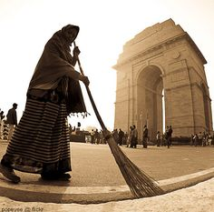 """India Gate. A woman cleaning the premises of India gate. India gate is a popular piece of architecture and is a site for the """"Tomb of Unknown Soldiers"""""""