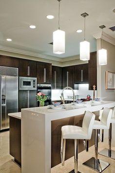 Cozinha americana com uma bela decoração, lustres super diferenciados, cadeiras lindas e modernas. Ambiente maravilhoso.