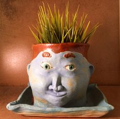 This guy is designed for your favorite succulents or plant that you want to display at work, home or your creative space.  He is made of high fire clay and fired to 2200 degrees.  There is also a drain hole in the side that allows excess water to drain to the tray.  This piece is approximately 8 wi