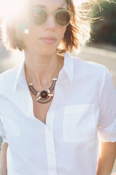 crisp white shirt and a black and gold statement necklace to dress it up. great work chic outfit