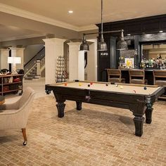 Remodeled basement with large living area, pool table, bar, exceptional brick flooring, and finely crafted molding
