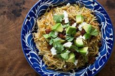 Sopa Seca de Fideo with Tomatillos- a version that used tomatillo sauce instead of a tomatoes, and garnished with goat cheese and chorizo,