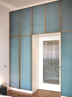 Gerahmte blaue Stoffpaneele betonen den Eingang zum Raum
